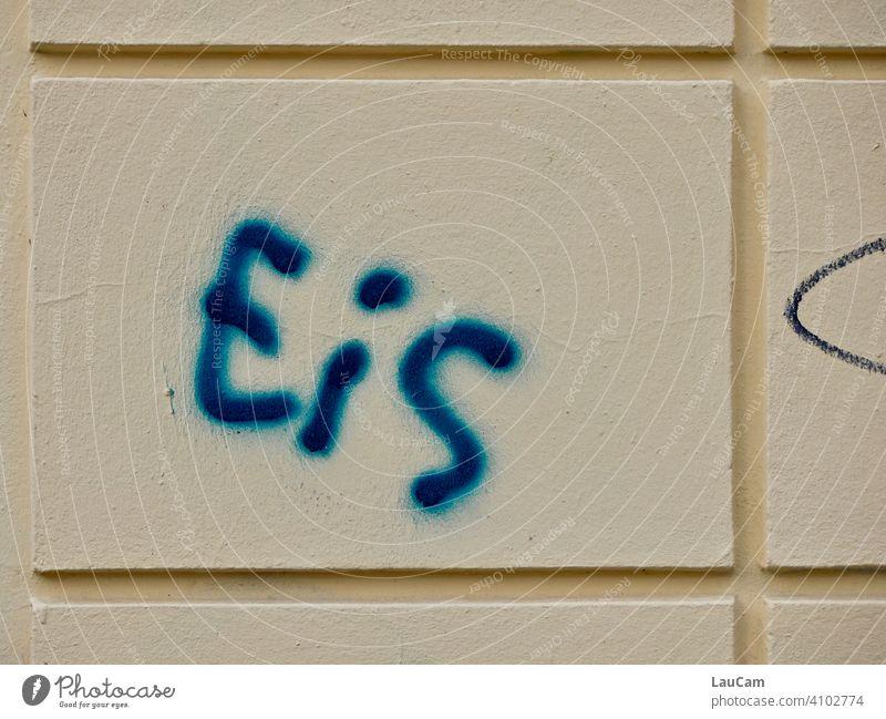 """Blauer Schriftzug """"Eis"""" auf heller Hausfassade Buchstaben Wort Fassade blau gelb Wand Graffiti Farbfoto Straßenkunst Schmiererei Mauer Text Schriftzeichen"""