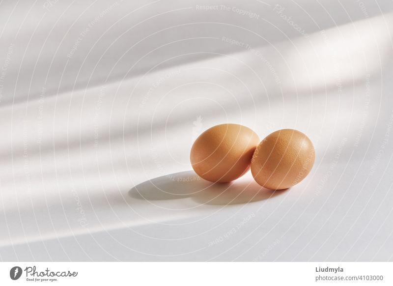 Zwei braune Eier auf einem weißen Hintergrund in natürlichem Sonnenlicht Schatten Federn zwei Produkt vorbereitet essen Feier Koch Mittagessen Raum Gruß frisch