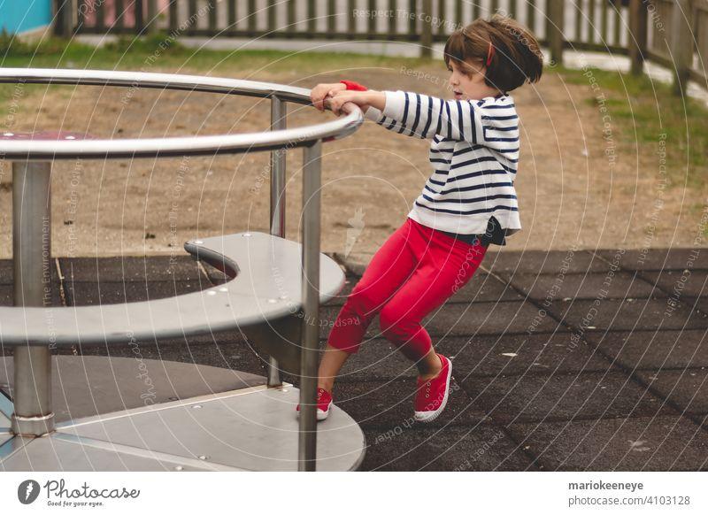 Seitenansicht eines kleinen Mädchens, das ein sich drehendes Karussell auf einem Spielplatz antreibt aktiv Aktivität Beweglichkeit Vergnügen amüsant Kaukasier
