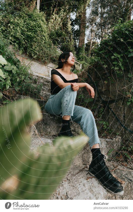 Junge schöne afrikanische Frau sitzt auf einigen Treppen auf Frühling Kleidung und Brille Amerikaner multikulturell jung ethnisch hispanisch Latein Model Haut