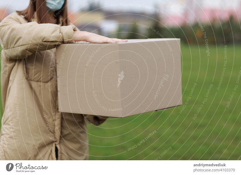 Lieferung Mädchen im Gesicht medizinische Maske halten leeren Karton im Freien auf einer Wohnanlage Hintergrund. Service Coronavirus. Online-Shopping. mock up.