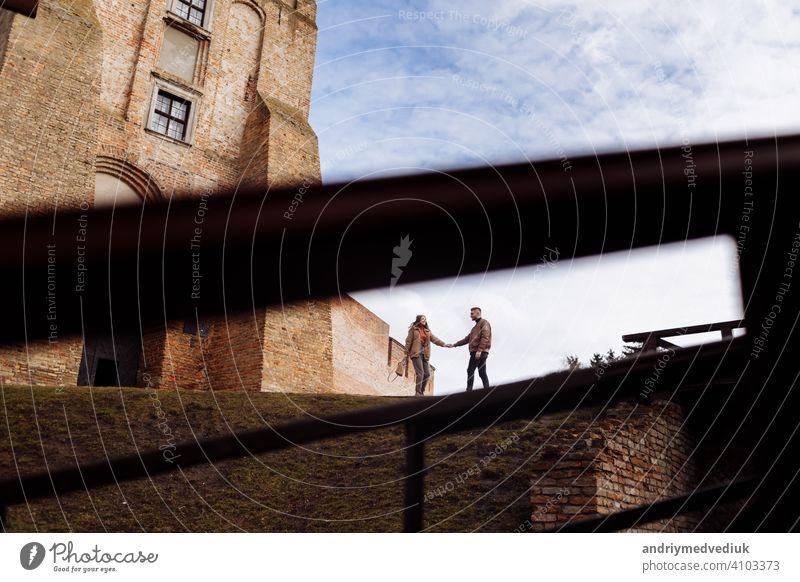 Attraktives junges Paar zu Fuß in der Nähe der Burg. Frau und Mann sind zu Fuß halten die Hände auf dem Hintergrund der alten Gebäude. Zwei lächelnde Liebende. selektiver Fokus