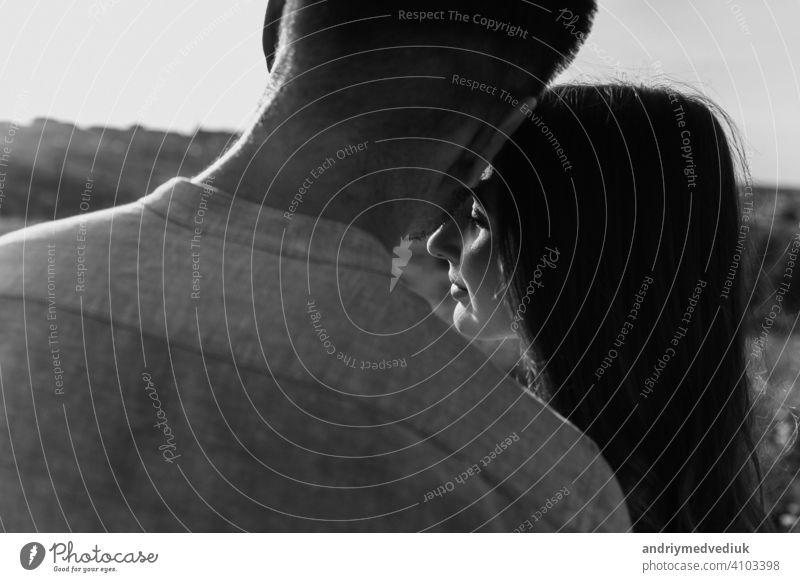 Schwarz-Weiß-Foto von jungen liebenden Paar umarmt draußen. Konzept des Glücks und der Liebe. Nahaufnahme Foto. Liebesgeschichte Porträt Saison Zusammensein