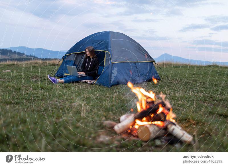 Mädchen mit Laptop in den Bergen. Tourist Frau verwendet einen Laptop in der Natur, Freiberufler Tippen auf einem Computer in der Nähe eines Zeltes in einer Reise vor dem Hintergrund einer Berglandschaft.