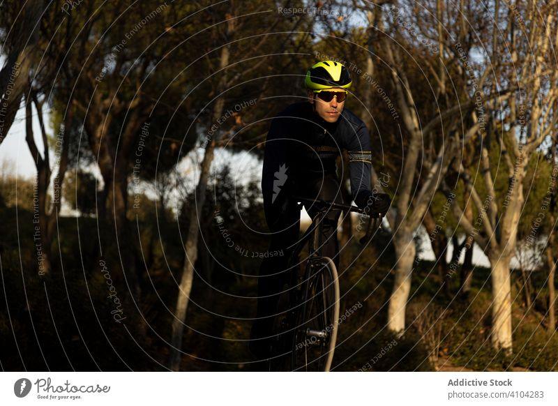 Mann radelt in einem Park Rennen Freiheit Schutzhelm Mitfahrgelegenheit Geschwindigkeit Fahrrad Zyklus Radfahrer Übung schnell Fitness Person Sport Abenteuer