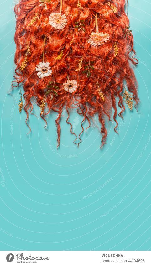 Roter Ingwer gebogene Haare Hintergrund mit Blumen auf türkisblauem Hintergrund. Schönheit und Haar-Styling-Konzept. rot gekrümmt Behaarung stylen grün Blätter
