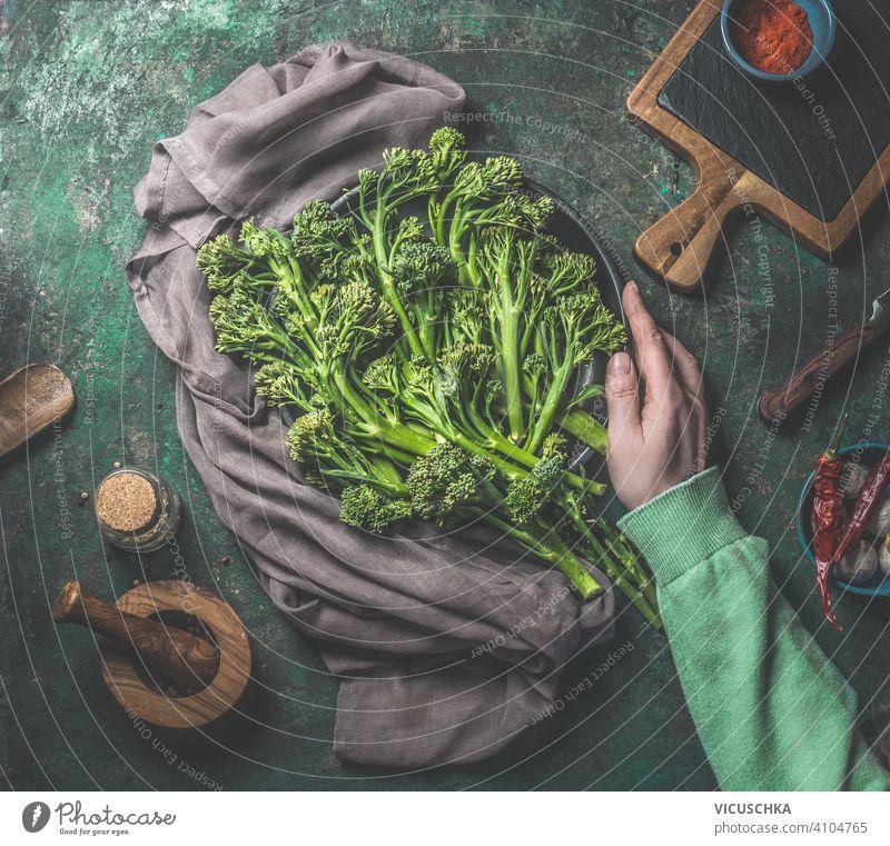 Frauenhand in grünem Sweatshirt hält wilden Brokkoli auf dunklem rustikalem Hintergrund. Ansicht von oben. Gesundes Essen Hand Beteiligung dunkel Draufsicht