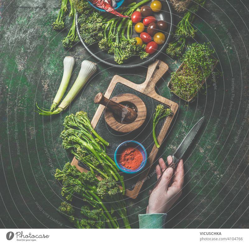 Kochen Vorbereitung der wilden Brokkoli. Frauen Hand hält Messer auf dunklen rustikalen Hintergrund mit Schneidebrett und Zutaten. Ansicht von oben. Gesundes Essen