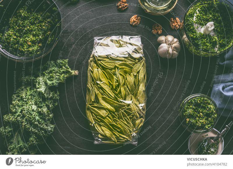 Grüne Nudeln in Plastikverpackung auf dunklem Küchentisch mit Grünkohl und anderen Zutaten. Ansicht von oben grün Spätzle Kunststoffverpackung dunkel Tisch Kale