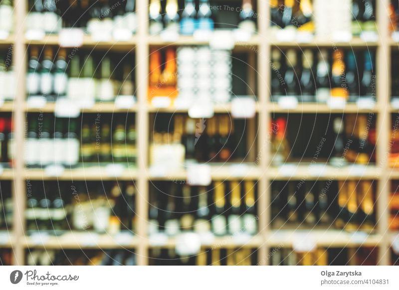 Unscharfes Bild von Flaschen mit Alkohol in den Regalen im Supermarkt. Wein Getränk Hintergrund abstrakt Einzelhandel Werkstatt Laden Weingut Ablage Markt Reihe