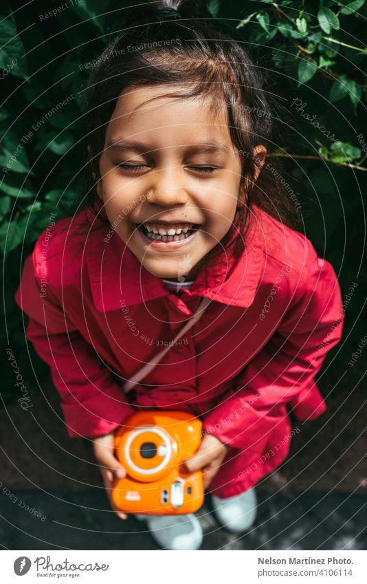Porträt eines kleinen hispanischen Mädchens, das einen fucsiafarbenen Mantel trägt und eine orangefarbene Vintage-Kamera hält Kindheit Menschen Freude Vergnügen