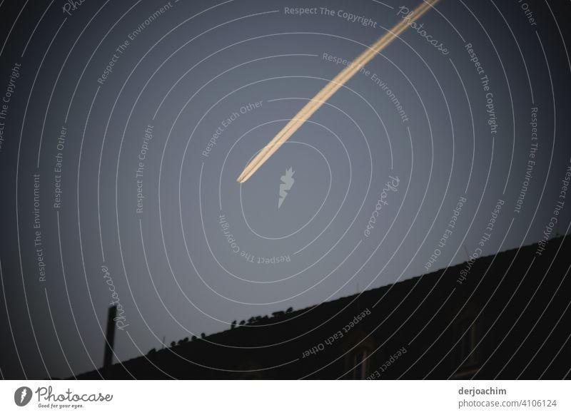 Geheimnisvolle Bewegung am Abend Himmel . Kontenzstreifen des Flugzeuges in großer Höhe über der Stadt... Wolkenloser Himmel Schönes Wetter Außenaufnahme