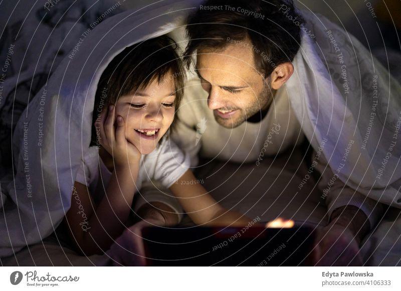 Vater und Sohn verwenden digitales Tablet zusammen nachts im Bett Schlafenszeit Nacht liegend Tablette digitales Tablett lesen Schlafzimmer unten Decke
