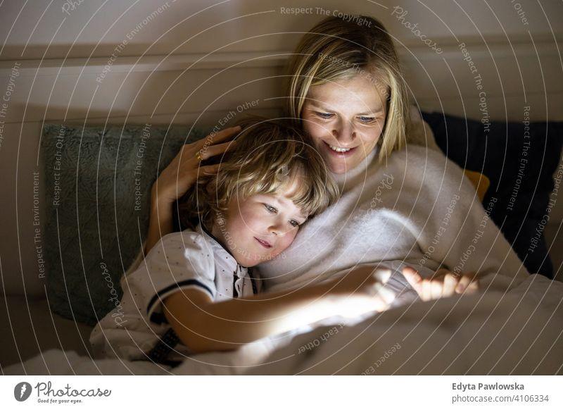 Mutter und Sohn verwenden digitale Tablette zusammen in der Nacht im Bett Schlafenszeit liegend digitales Tablett lesen Schlafzimmer Geschichtenerzählen
