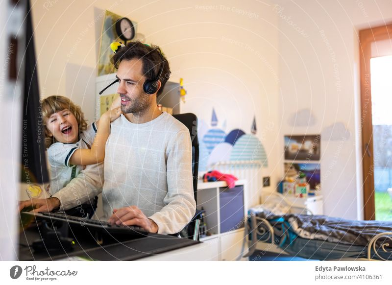 Junger Mann arbeitet von zu Hause aus mit seinem kleinen Sohn als Firma alleinerziehender Vater arbeiten Arbeiten zu Hause Computer beschäftigt Laptop