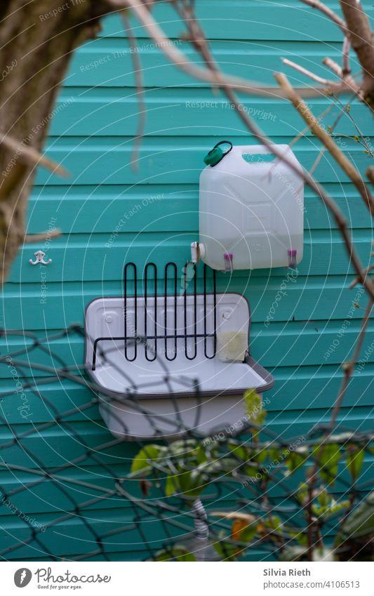 Außenwaschbecken bei einer Gartenlaube Schrebergarten Hütte Gartenhütte Außenaufnahme Menschenleer Farbfoto Gartenhaus Tag Natur Türkis Kanister Waschbecken