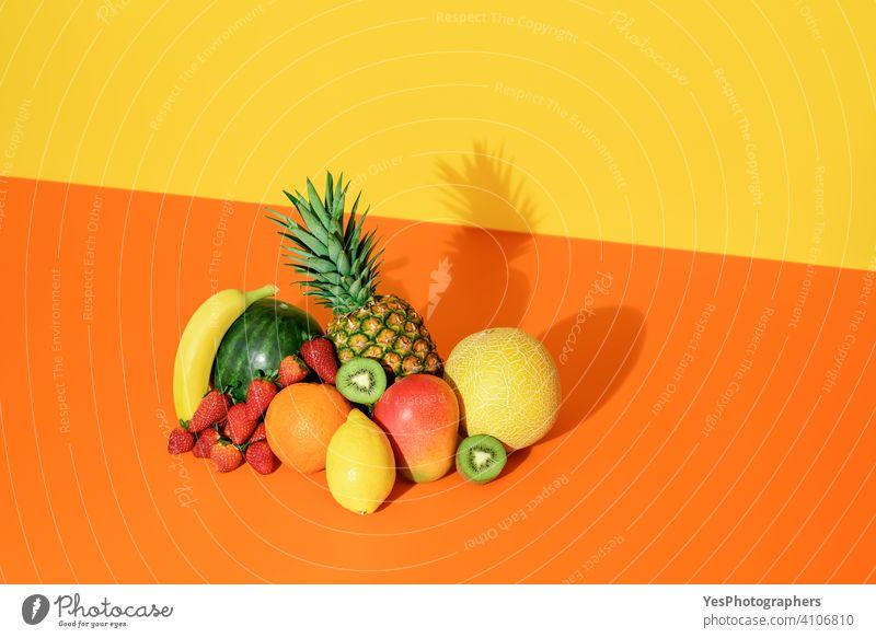 Tropische Früchte isoliert auf einem farbigen Hintergrund. Frische Sommerfrüchte. Ananas sortiert Banane Kantalupe Zitrusfrüchte farbenfroh Farben Textfreiraum
