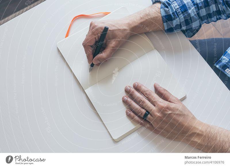 Mann schreibt in Notizbuch mit Füllfederhalter auf weißem Tisch Hand schreiben Schriftsteller Unterschrift Schreibtisch Menschen klassisch teuer schwarz Design