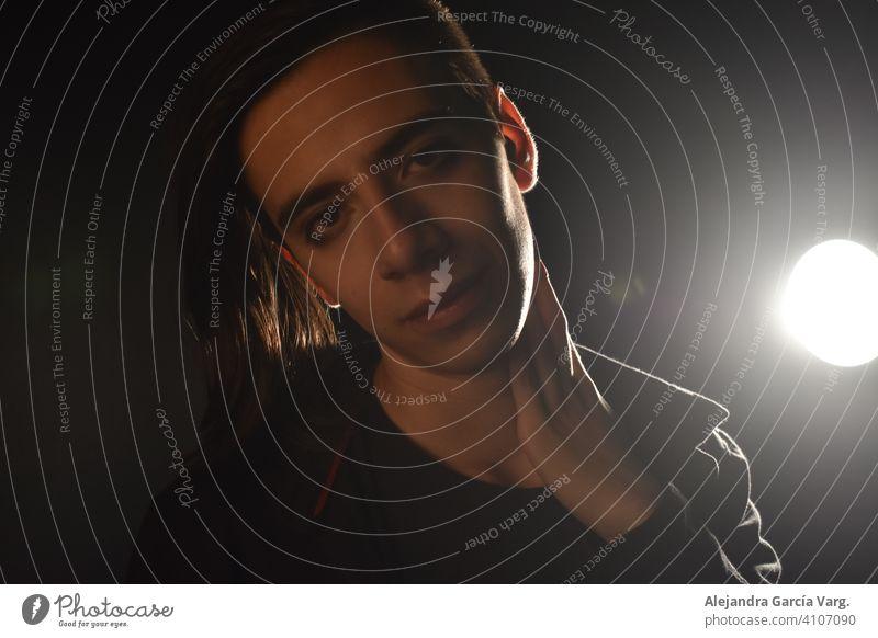 Langhaariger junger gut aussehender Mann auf schwarzem Hintergrund, dessen Gesicht von einem Licht beleuchtet wird, mit einem koketten Ausdruck für die Kamera, der ein leichtes Lächeln zeigt
