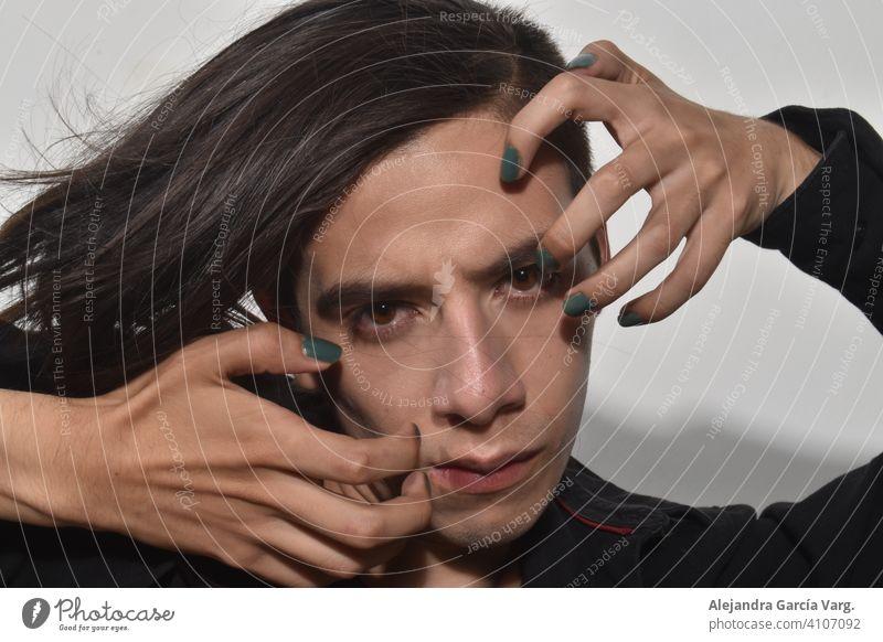 Gutaussehender junger Mann mit langen braunen Haaren, grün lackierten Nägeln, mit durchdringendem Blick und ernstem Gesichtsausdruck, starrer Blick in Großaufnahme
