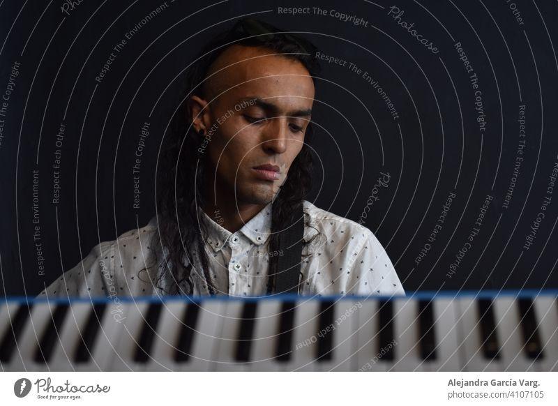 Konzeptuelle Musikfotografie, Tasten des Klaviers im Vordergrund mit einem langhaarigen Mann Musiker im Hintergrund mit einem friedlichen Ausdruck, schwarzer Hintergrund