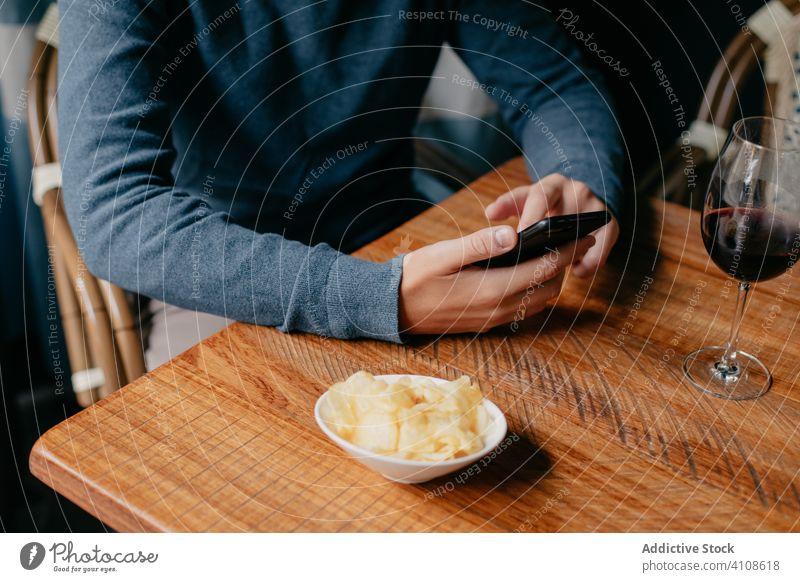 Mann benutzt Smartphone in einem Cafe benutzend Café Tisch Telefon Wein trinken ruhen sich[Akk] entspannen männlich Getränk Restaurant lässig Gerät Apparatur