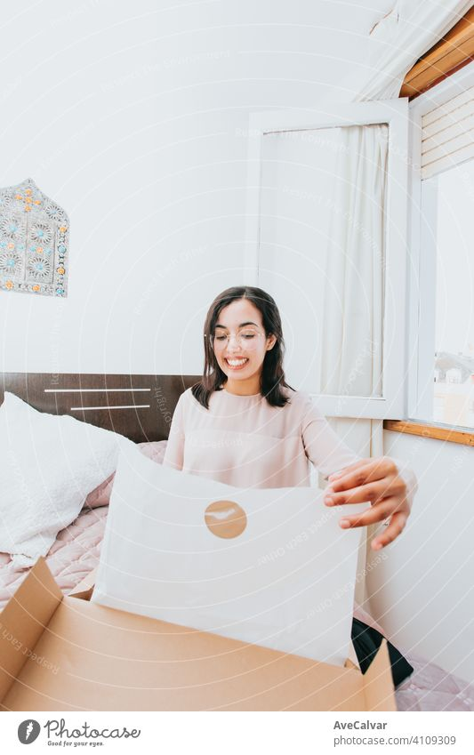 Junge arabische Frau, die eine Box mit Produkten öffnet, während sie lächelt, Konzept Einzelhandel und Online-Kauf Eröffnung im Innenbereich Versand kaufen