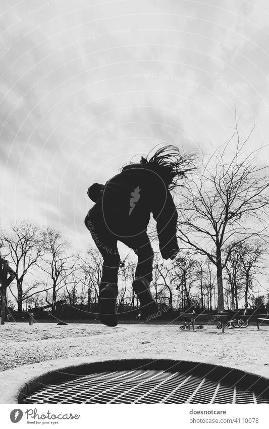 Silhouette eines Mädchens, dass auf einem Trampolin springt springen Spielplatz spielen Trampolinspringen Kind Spaß Freude Lebensfreude Sport Freizeit Kindheit