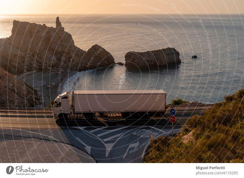 Lkw mit Kühlsattelauflieger fährt auf einer Straße neben einem Strand. camion Refrigerado montaña Farbfoto Menschenleer Natur blau Karretera Playa mar Islote