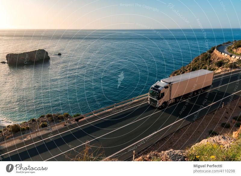 LKW mit Kühlsattelauflieger fährt auf einer Straße am Meer. camion Refigerado mar Anhänger Playa Transporte Perecederos remolque Karretera montaña Logística