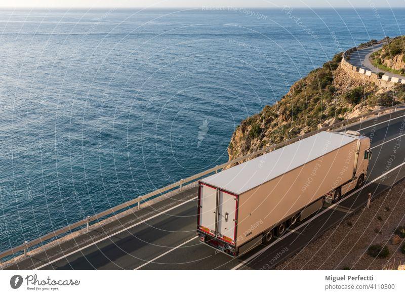 LKW mit Kühlsattelauflieger fährt auf einer Straße am Meer. camion Refigerado Temperaturregler Logística Transporte Transportar paisaje mar azul Vertrieb