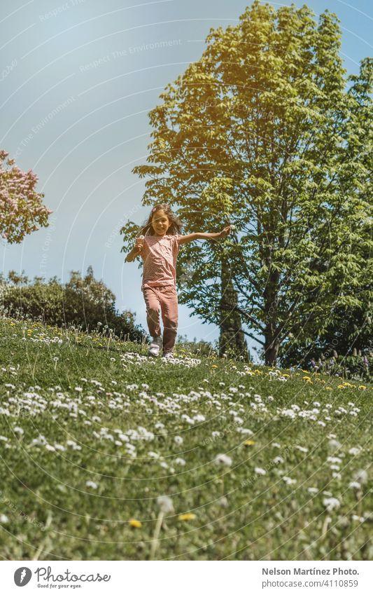 Porträt eines kleinen hispanischen Mädchens, das im Sommer im Park spielt und läuft. Genuss Hintergrund Tag spielen grün Freiheit offen Blume blasend Aktivität