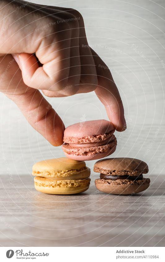 Crop Hand platziert Makronen auf dem Tisch Mann Platzierung Finger Haufen Biskuit frisch geschmackvoll Keks hell Bestandteil Lebensmittel gebacken süß Snack