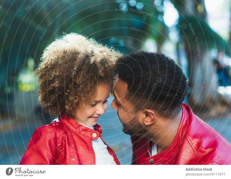 Glückliches kleines Mädchen umarmt Papa im Park Vater Tochter Umarmung Zusammensein Lächeln Straße Liebe ähnlich urban Kind Mann ethnisch wenig Partnerschaft