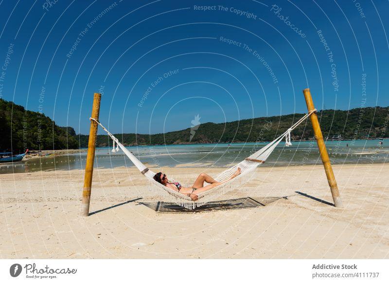 Ausruhende Frau in Hängematte am Strand sich[Akk] entspannen Sommer Sand Urlaub Natur Himmel Meer genießen tropisch Paradies MEER Sonne Lifestyle Badeanzug