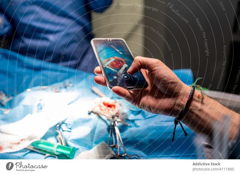 Mann fotografiert mit Smartphone, während medizinisches Personal Patienten in einer modernen Klinik operiert Chirurg Chirurgie Krankenhaus Sanitäter Hand Handy