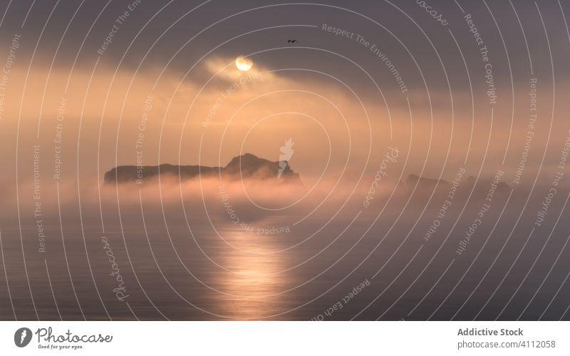Sonnenuntergang bewölkter Himmel über ruhiger See MEER Natur Klippe rau Licht hell Cloud Nebel Landschaft Abend Wasser reisen Abenddämmerung malerisch friedlich