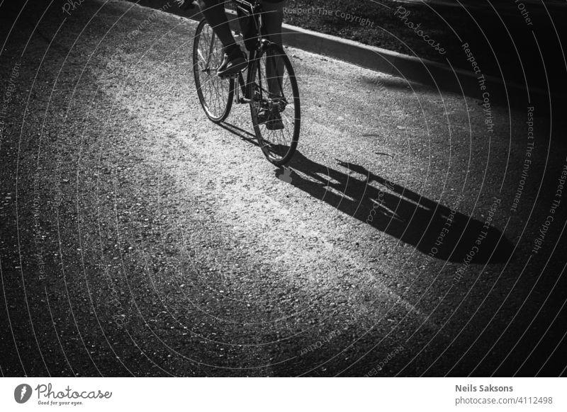 Schatten eines Mannes, der auf der Straße Fahrrad fährt. Aktion Aktivität Asphalt Gleichgewicht Radfahren Erwachsener Großstadt niedlich Zyklus Übung Spaß