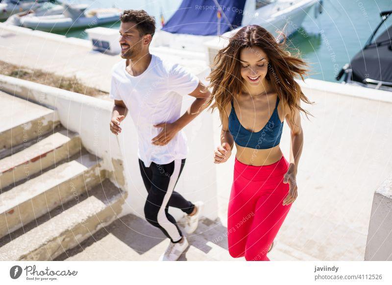Sportliches Paar trainiert hart, indem es gemeinsam im Freien Treppen hochläuft. rennen Fitness Schritt Training Frau Mann Mädchen passen Aktivität jung