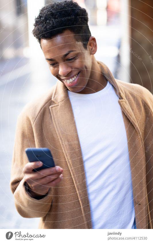 Junger schwarzer Mann, der sein Smartphone im Freien benutzt. männlich Kubaner jung Person Lächeln Glück Schüler Telefon lässig Lifestyle klug T-Shirt