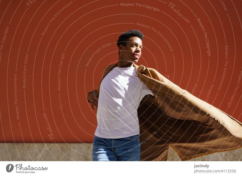 Junger schwarzer Mann tanzt auf roter Stadtmauer. Tanzen Straße Fröhlichkeit männlich Kubaner jung Ausdruck Person Glück Blick Tänzer im Freien eine Freude