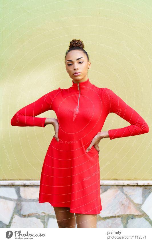 Junge schwarze Frau in rotem Kleid mit ernstem Gesichtsausdruck im städtischen Hintergrund. Schleife Frisur Behaarung Model Schönheit hübsch Porträt Mädchen