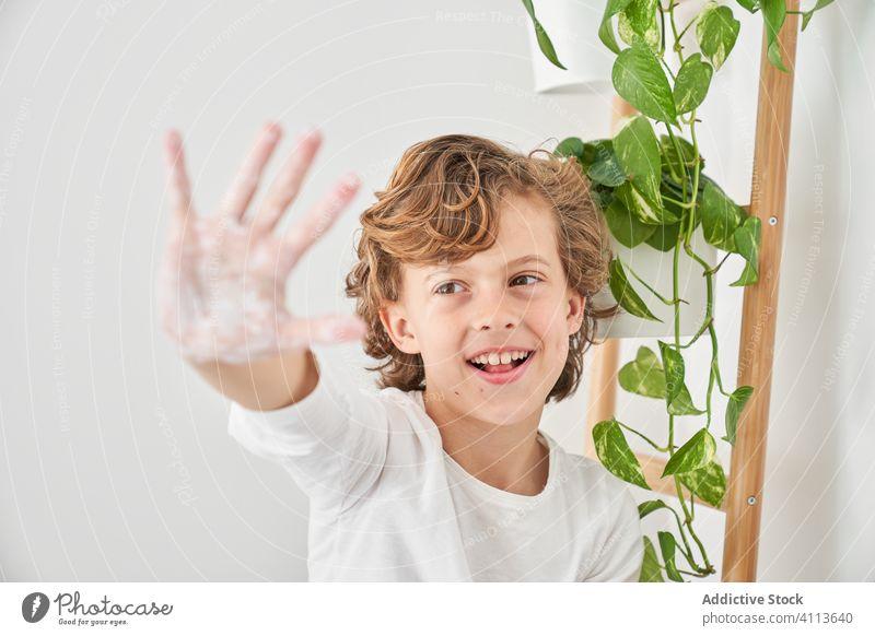 Blondes Kind wäscht sich die Hände in der Küchenspüle, um eine Infektion zu vermeiden Waschbecken Lifestyle Wäsche waschen im Innenbereich Sohn Junge Wasser