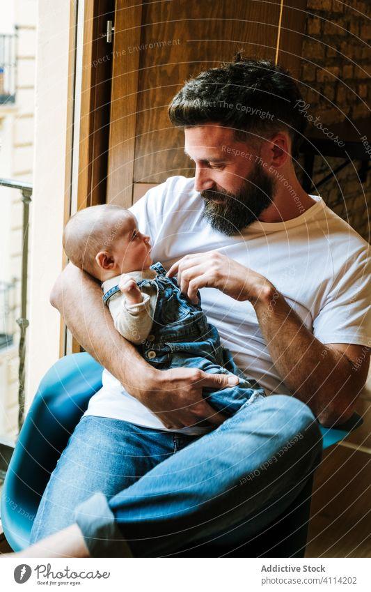 Bärtiger Vater kommuniziert mit Baby Kommunizieren Umarmung heimwärts Liebe Angebot Fenster sitzen gemütlich Stuhl Mann Säugling Kind wenig Umarmen Eltern