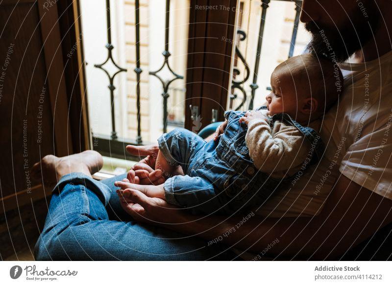 Bärtiger Vater mit Baby am Fenster sitzend Vollbart Kommunizieren Umarmung heimwärts Liebe Angebot gemütlich Stuhl Mann Säugling Kind wenig Umarmen Eltern