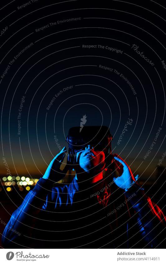 Junger Mann erforscht virtuelle Realität Nacht VR dunkel Straße Headset Schutzbrille futuristisch leuchten neonfarbig rot Licht männlich modern Gerät Apparatur