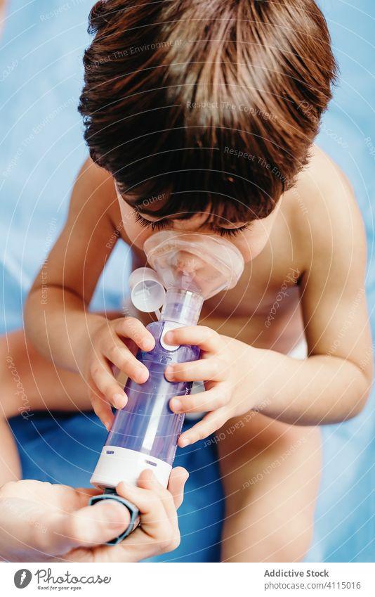 Kranker Junge erhält Inhalationsbehandlung in der Klinik Kind inhalieren Atmung krank Leckerbissen Medizin medizinisch Atemwegserkrankungen Arzt Mundschutz