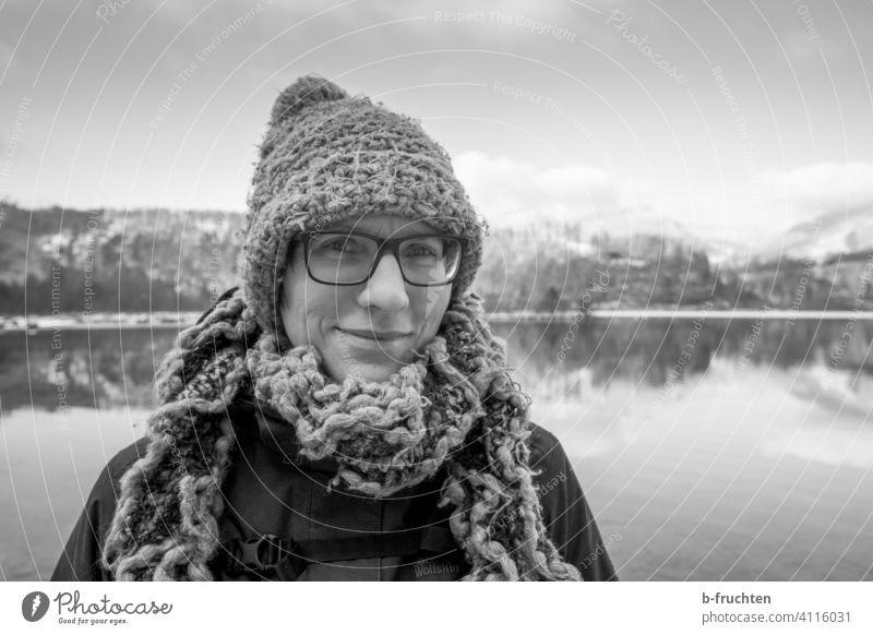 Frau mit Wollmütze und Wollschal vor einem Gebirgssee Portrait Schal Wolle Mütze Winter kalt See Seeufer Porträt Gesicht Erwachsene Bekleidung Alpen Brille
