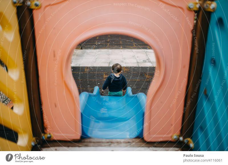 Rückansicht eines auf dem Spielplatz spielenden Kindes 1-3 Jahre Sliden Park Freude Kleinkind Tag Farbfoto Mensch Kindheit Außenaufnahme Spielen farbenfroh