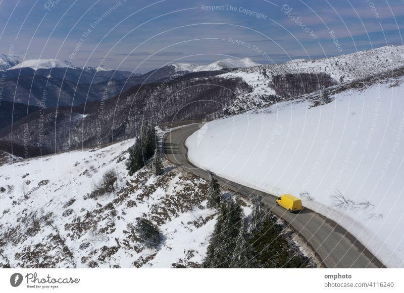 Microbus-LKW, der sich auf einer Winterstraße in den Bergen bewegt Lastwagen PKW Schnee Berge u. Gebirge Fahrzeug gelb verschneite Straße weiß Laufwerk